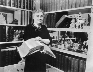 1956: Portrait of American writer, educator and advocate for the disabled Helen Keller (1880 - 1968) holding a Braille volume and surrounded by shelves containing books and decorative figurines. A childhood illness left Keller blind, deaf and mute. (Photo by Hulton Archive/Getty Images)